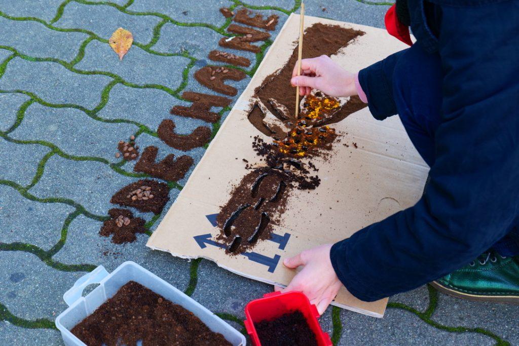 Farbfoto. Person kniet am Boden und arbeitet mit Pinsel an der unteren mit Kaffeepulver gefüllten Schablone. Zwei gefüllte Dosen stehen daneben.