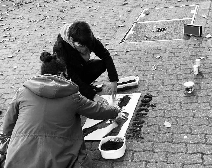 Schwarz-weiß-Foto. Zwei Personen knien am Boden. Sie füllen die Schablonen mit Kaffeepulver. Neben ihn steht ein Lautsprecher und Schalen mit Kaffeepulver.