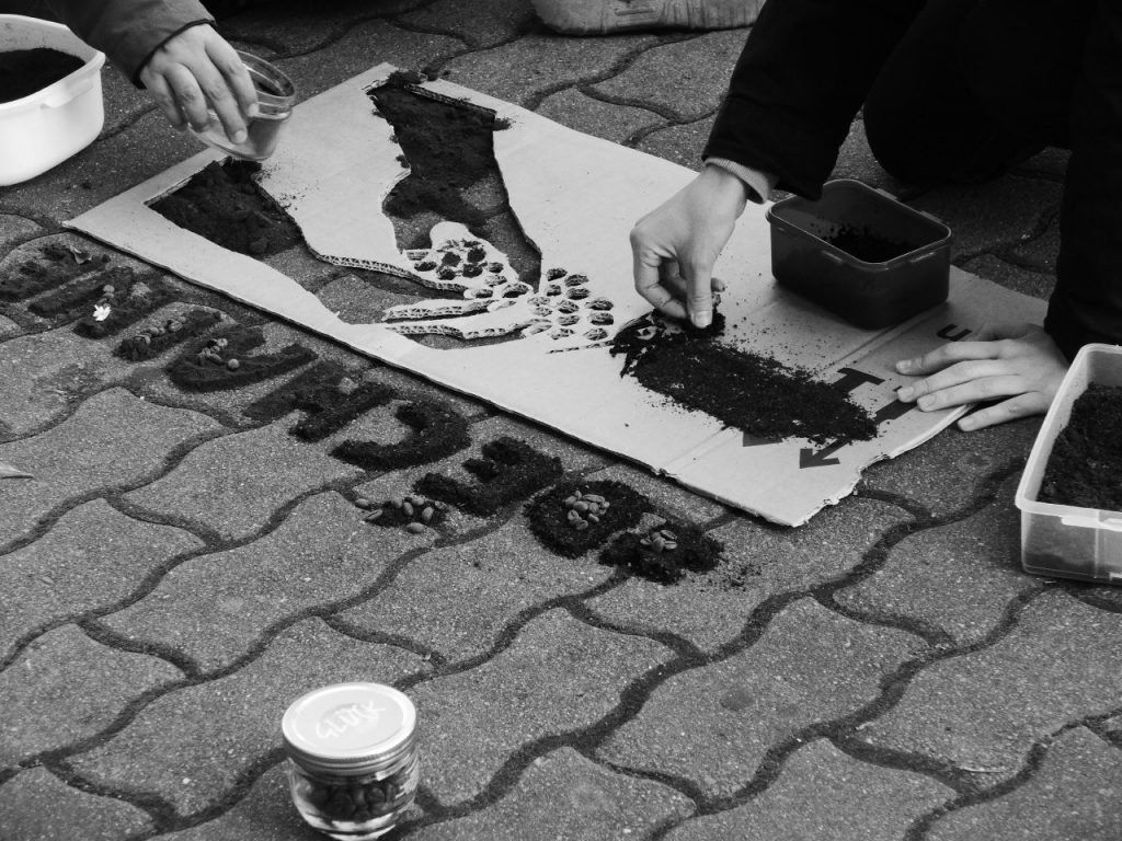 Schwarzweiß-Foto. Gehweg. Darauf liegt ein Schablome. Hände von zwei Personen füllen die Schablone mit Kaffeepulver..