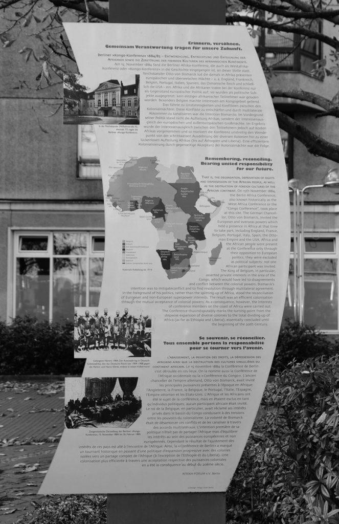 Schwarzweiß-Foto. Es zeigt die Gedenktafel der Berlin-Kongokonferenz im Berliner Stadtbild. Der Text auf der Tafel ist auf deutsch, englisch und französich. Text findet sich hier: www.gedenktafeln-in-berlin.de/nc/gedenktafeln/gedenktafel-anzeige/tid/berliner-afrika-konf