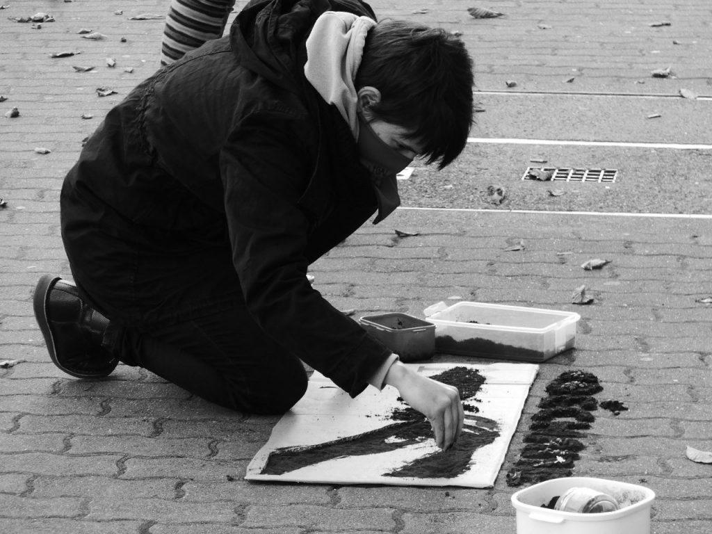 Das Foto ist schwarz-weiß. Eine Person kniet am Boden und füllt eine Schablone mit Kaffeepulver. Die Person trägt ein Tuch vor dem Mund.