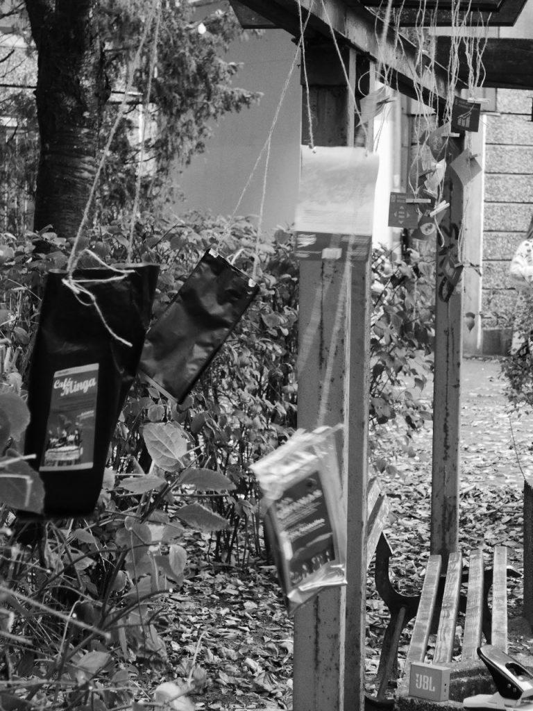 Ein schwarz-weiß Foto. An Seilen an einer Rankenhilfe aufgehangene Kaffeeverpackungen und Papierquadrate mit SDG-Iconsauf unterschiedlichen Höhen flattern im Wind.